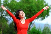 Happy young woman with opened hands feeling free outdoors