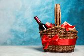 Gift Basket With Bottle Of Wine On Color Background. Space For Text poster