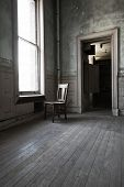 stock photo of wainscoting  - A solitary chair facing the window in a abandoned room with old wood floors and high ceiling - JPG