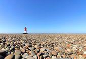 Faro con guijarros de la playa en primer plano