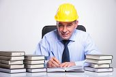 senior business man with helmet sitting at his desk, among piles of books and writing while smiling to the camera. on gray background