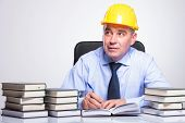 senior business man with helmet, sitting at a desk full of books and writing while contemplating, looking away from the camera. on gray background