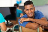handsome male indian high school student looking back in classroom