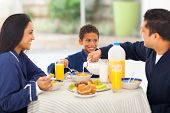 loving father pouring milk in his son's corn flakes during breakfast