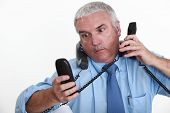 businessman overwhelmed with phone calls