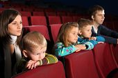 Young family of five people watching a movie
