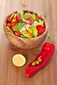 foto of iceberg lettuce  - Bowl made of olive wood filled with cos and iceberg lettuce salad with paprica carrots tomatoes and green olives on wooden table - JPG