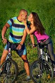 Lovely couple riding bikes in field