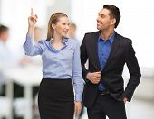 bright picture of man and woman pointing finger in office