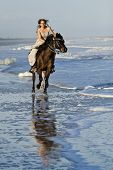 woman in formal dress riding galloping horse through surf.