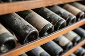 stock photo of bottles  - ancient wine bottles dusting in an underground cellar - JPG