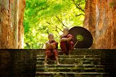 image of prayer  - Young Buddhist monk reading outdoors - JPG