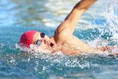 Man swimmer swimming crawl in blue water. Portrait of an athletic young male triathlete swimming cra