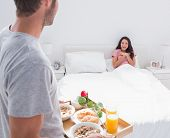 Man bringing breakfast to his impressed wife in bed