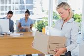 Businesswoman leaving office after being laid off carrying box of belongings