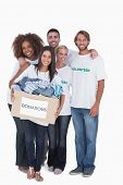 Happy group of volunteers holding donation box on white background