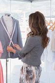Young fashion designer measuring blazer lapel