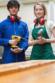 stock photo of workbench  - Woodworking students standing before a workbench and holding a driller and a hammer - JPG