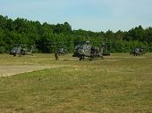stock photo of apache  - Four Apache Helicopters and crew on a grass airfield - JPG