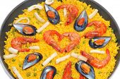 closeup of a typical spanish paella, with seafood and vegetables, in a paellera, the paella pan, on a white background