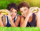 Closeup portrait of two happy boys eating big tasty fatty burgers outdoors, lying down on green field and enjoying sandwich with cheese, meat and vegetables