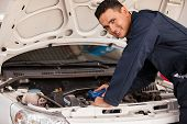 stock photo of hoods  - Happy young mechanic pouring some new oil into a car - JPG