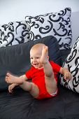 Lovely blond baby sitting on a sofa in the living room
