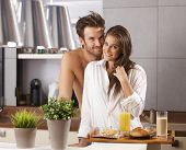 Morning portrait of happy loving couple in the kitchen with breakfast.
