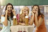 Pretty girls having fun, forming moustache from hair, drinking beer in outdoor bar, smiling.