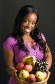 Mujer afroamericana bastante hispana con saludable plato de fruta fresca