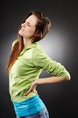 stock photo of hernia  - Studio shot of a young woman having a severe lumbar pain over grey background - JPG