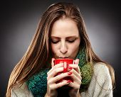 picture of freezing temperatures  - Closeup of a woman with flu wrapped up in a scarf and drinking hot tea over gray background - JPG