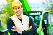 stock photo of machinery  - Builder or driver standing in front of construction machinery on building site - JPG