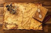Sextant, old book and glasses on vintage map over wooden background