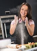 Young woman having fun with flour while making dough on a modern kitchen