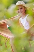 Summer joy, hammock - girl with a book resting on a hammock in the garden