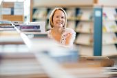 image of librarian  - Portrait of confident female librarian working in library - JPG