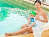 Baby and mother are sitting on the edge of a pool