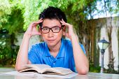 Young Chinese Asian student is bored at home with difficult homework assignment for school next day