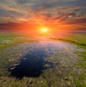 sunset on small lake in steppe
