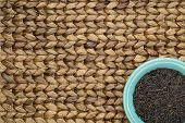 a ceramic bowl of wild rice grain against a water hyacinth woven mat with a copy space