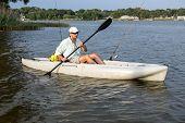 Man Fishing and Paddling in Kayak