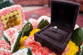 picture of jewel-case  - A diamond wedding ring in an open box on traditional Thai style garland - JPG