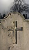 image of headstones  - Spooky old weathered headstone in a foggy graveyard - JPG