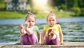 image of identical twin girls  - Twing girls are exercising on a lake shore - JPG