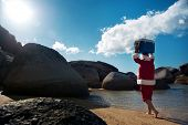 Man in Santa Claus costume walking along the beach with his Cooler on his head with copyspace