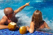 foto of hot-tub  - Romantic couple with coconut drink relaxing in hot tub - JPG