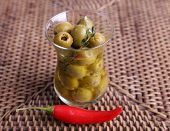 Green olives in oil with spices and chili in glass on table