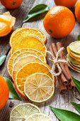 Dried Orange And Lemon Slices, Cinnamon Sticks And Ripe Tangerines On Old Table.