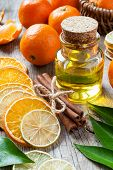 Bottle Of Essential Citrus Oil, Dried Orange And Lemon Slices, Cinnamon Sticks And Ripe Tangerines O